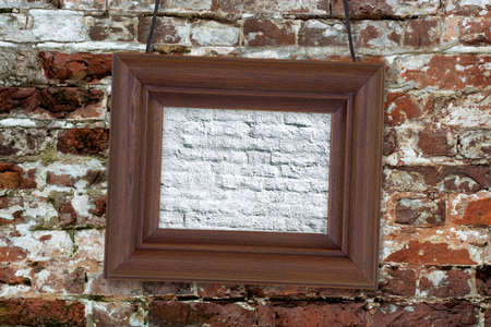Painting in wooden frame hanging on an old brick wall photo