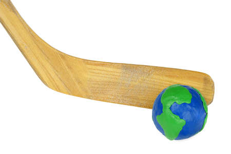 A fragment of a hockey stick with plasticine globe on white background photo