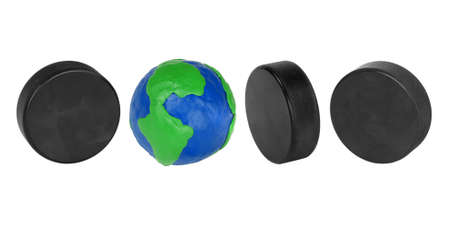 Plasticine globe and hockey puck on a white background photo