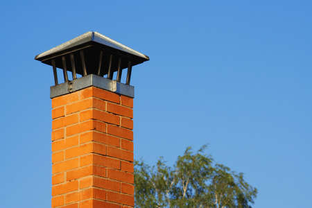 cement chimney: Brick chimney against the tree and the blue sky Stock Photo