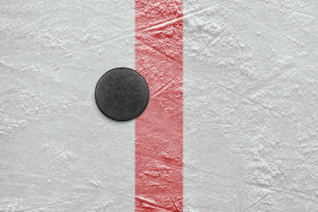 Puck lying on the red goal line. Texture, background Stock Photo