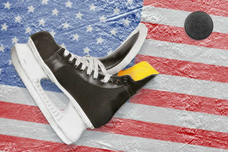Puck, skates and the image of the American flag on the ice