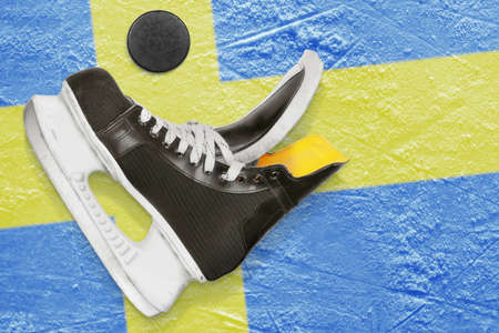 Puck, skates and the Swedish flag on the ice photo