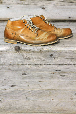 stoking: A pair of old leather boots on background wooden wall of a house