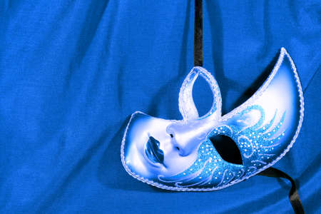 Festive carnival mask on the background of blue fabric photo