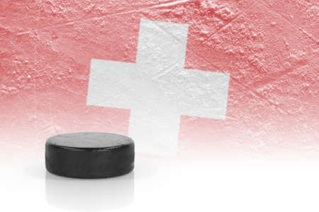 Hockey puck and the image of the Swiss flag. Concept photo