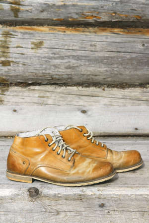 stoking: Pair of old leather shoes on a wooden wall background Stock Photo
