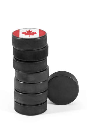 Canadian ice hockey pucks stacked on a white background Stock Photo
