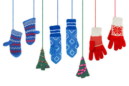 woman hanging toy: Three pairs of knitted, woolen mittens and a pair of Christmas trees