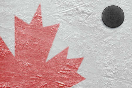 ice arena: Fragment of the image of the Canadian flag on a hockey rink and puck Stock Photo