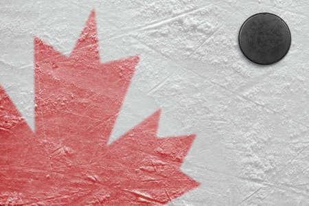 hockey sobre hielo: Fragmento de la imagen de la bandera canadiense en una pista de hockey y el puck