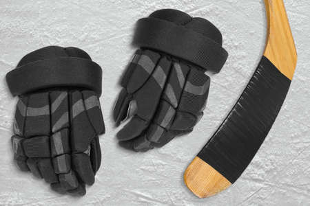 ice arena: Hockey gloves and stick on the ice arena. Texture, background