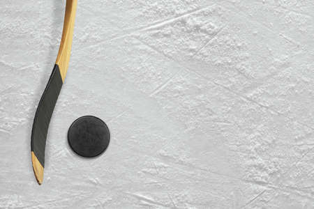 Hockey puck and stick on the ice arena. Texture, background
