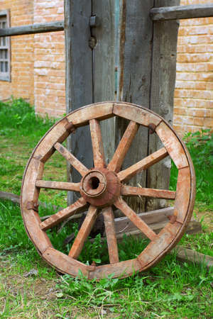 wheel house: The old wagon wheel in the yard of a village house. Texture, background