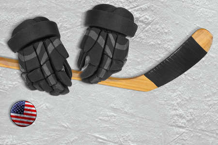 ice arena: American hockey puck, stick and gloves on the ice arena. Concept