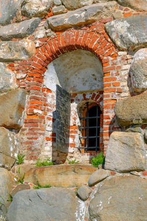 A fragment of the old wall with window and bars. City, architecture, exterior