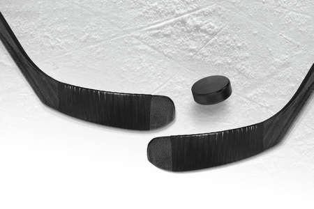Hockey puck and two black sticks on the ice hockey rink. Hockey, concept