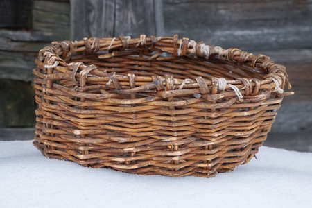 Old wicker basket on the table in the courtyard of a village house