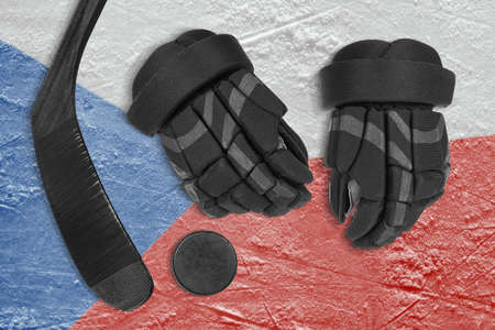 Hockey puck, stick, gloves and the Czech flag image on the arena ice