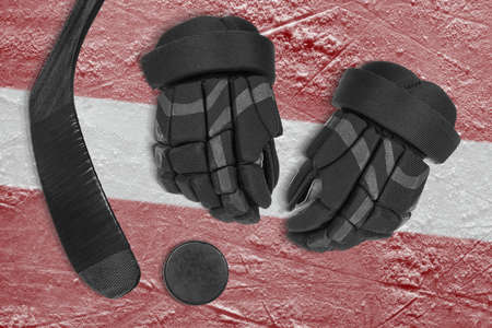 Hockey puck, stick, gloves and the image of the Latvian flag on the ice of the sports arena