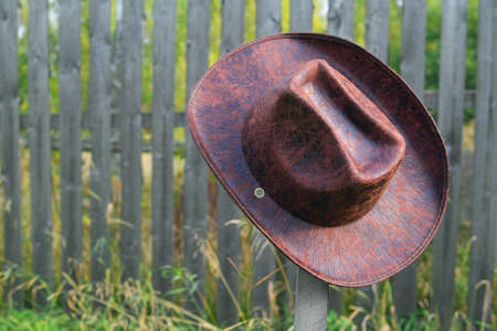 A leather hat with wide brims hanging on a wooden pole