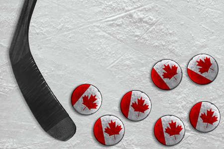 Stick and Canadian washers on the ice of the hockey field. Concept, background, hockey Stock Photo