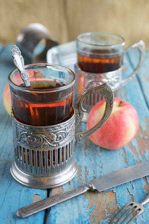 Two glasses of tea, old cutlery and apples on a wooden table. Texture, background Stock Photo
