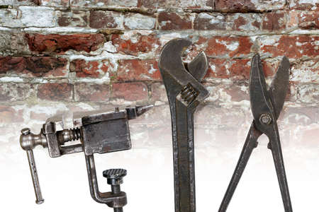 Old metalwork tools on a brick wall background