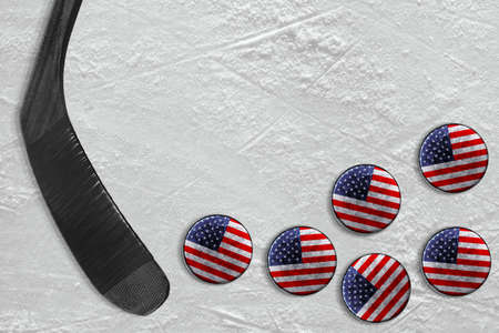 The stick and the American washers on the ice of the hockey field. Concept, background, hockey Stock Photo