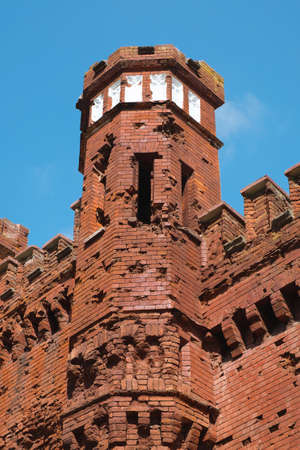 Fragment of the fortress tower against the blue sky. Architecture, fortification, exterior
