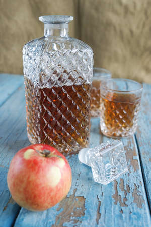 vintage furniture: Decanter, glasses and apple on the old wooden table. Crockery, alcohol, exterior