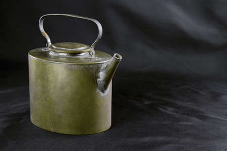 An old maroon teapot on a black cloth background. Texture, background