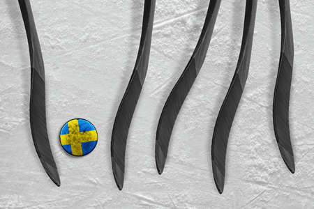 The Swedish puck and five sticks on the ice of the hockey arena. Concept, hockey Stock Photo