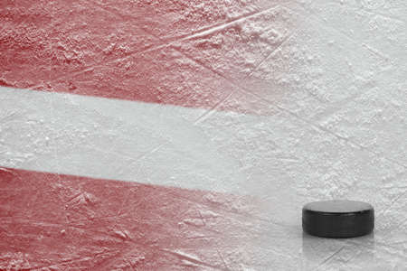 Hockey puck and the image of the Latvian flag on the ice. Concept, hockey