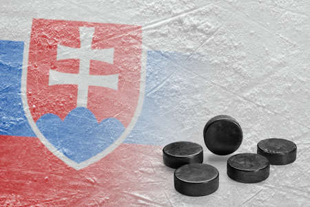 Image of the Slovak flag on ice and hockey pucks. Concept, hockey Фото со стока
