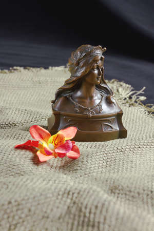 Flower and old bronze bust on the table. Still life, subject, exterior Фото со стока