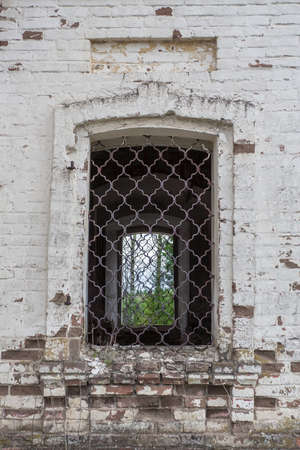 Fragment of an old church wall with a window and bars. Background, architecture