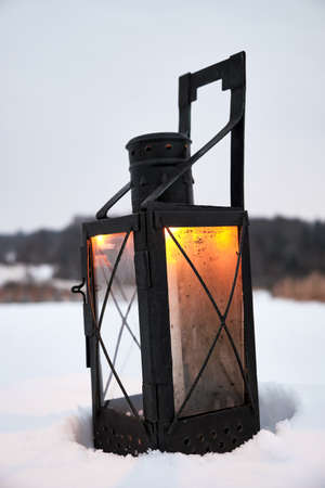 Old metal lamp with a candle on a snowy field Stock Photo