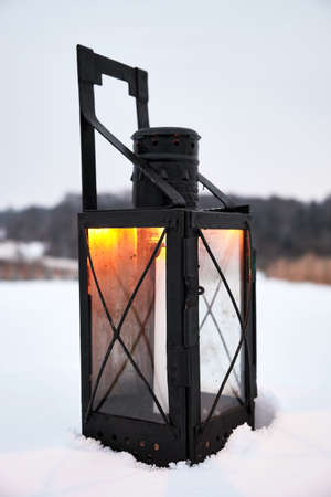 Old metal lamp with a candle in the yard of the house