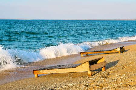 Sandy coast of the Azov Sea and old sun lounger