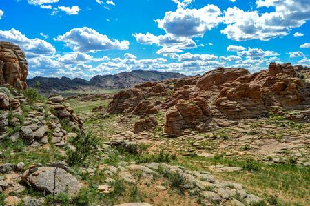 Mongolian valley covered with large flat red-rock formations. Stock Photo