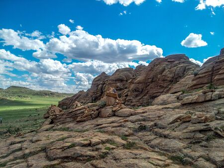 Huge Flat Rock Formation with several small piles of rocks called Ovoos in Mongolian valley.