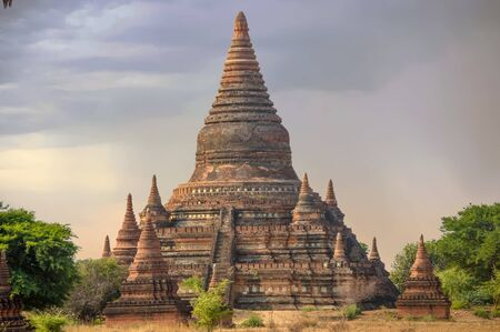 Tall Stupa Surrounded by Mini-Pagodas at Sunrise In Bagans Field of Temples Stock Photo