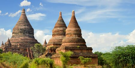 Grouping of 3 Hershey-Kiss Shaped Stupas Together in Began Field of Temples Stock Photo