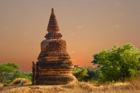 Singular Reddish Stupa In Dry Grass Area At Sunrise Bagan, Myanmar