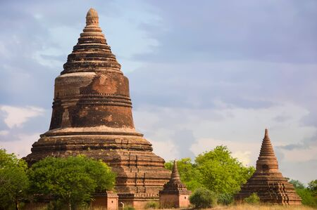 Big Reddish Bell Stupa With A Few Pagodas Near By in the 1,000-year-old archaeological theme park of Bagan Stock Photo