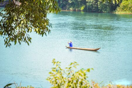 Hsipaw, Myanmar - May 7, 2016 Lone Man Paddeling In A Canoe Down A River in Hsipaw Stock Photo
