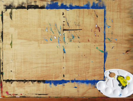 canva: wooden easel with art palette on empty canvas