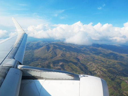 Wing of the plane on blue sky, clouds and mountains background