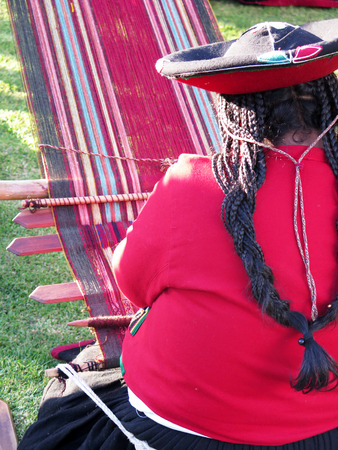 Close up of Peruvian lady in authentic dress spinning yarn by hand. (Peru)